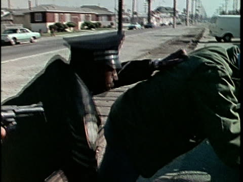 1970s MONTAGE Two police officers arresting man on street, Los Angeles, California, USA, AUDIO