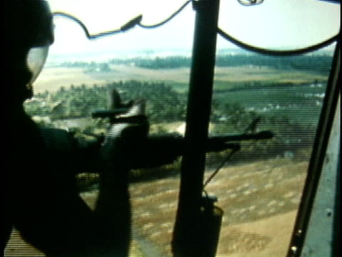 1970s montage us military helicopter flying over vietnamese countryside / american soldier shooting machine gun from helicopter during vietnam war /... - vietnamkrieg stock-videos und b-roll-filmmaterial
