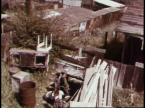 vídeos de stock, filmes e b-roll de 1970s montage watts housing including a little girl with her fingers in her mouth standing in a yard containing a rusty barrel and junk / watts... - condição