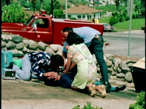 1970s MONTAGE Woman giving CPR as paramedics attend to patient, Los Angeles, California, USA, AUDIO