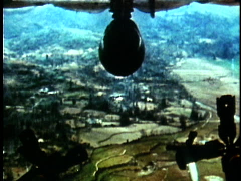 1970s ms slo mo napalm bombs dropping from us bomber plane over countyrside during the vietnam war / vietnam - vietnam war stock videos & royalty-free footage