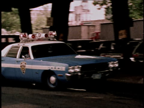 1970s WS Police car with siren and lights flashing turning corner / Brooklyn, New York, United States