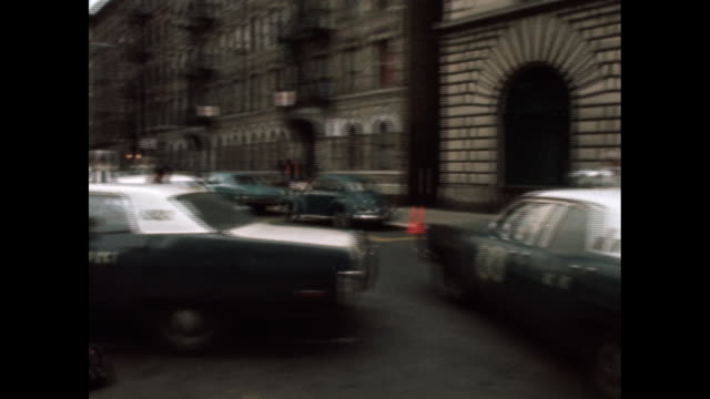 1970s police officer walks from station to his police car and camera pans back to the station in the bronx. - police station stock videos & royalty-free footage