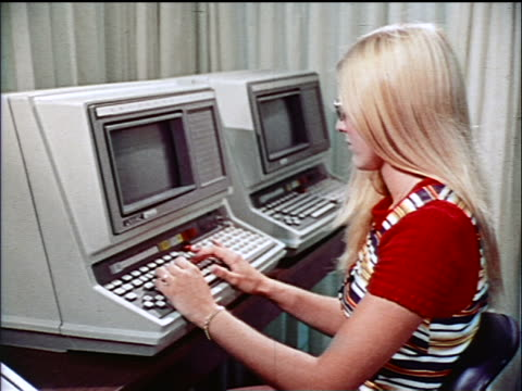 vídeos de stock e filmes b-roll de 1970s profile blonde woman typing on computer in office / educational - estilo retro