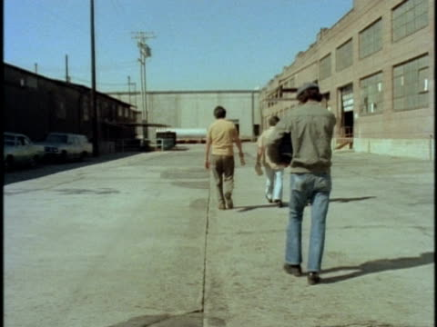 1970s WS CS HA Rear view of four workers walking towards factory entrance, Los Angeles, California, USA, AUDIO