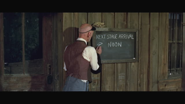 1970s MS Stage line clerk changing arrival time on time schedule board