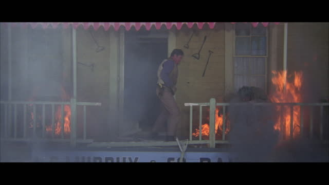 1970s WS Two cowboys fighting amidst fire