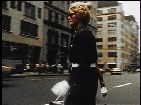 vídeos y material grabado en eventos de stock de 1970s two middle-aged women in dresses, sunglasses + gloves carrying purses crossing nyc street - 1970
