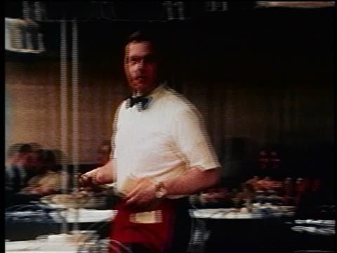 1970s waiter carrying menus walking past tables looking at camera at outdoor cafe / NYC / doc.