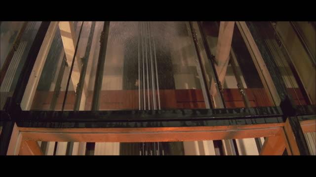 1970s ms la water being poured onto fire in elevator shaft - breitwandformat stock-videos und b-roll-filmmaterial