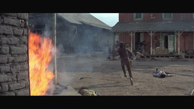 1970s WS Western town street with dead bodies on ground, buildings on fire and cowboys running around