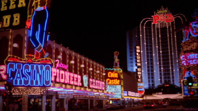 1970s wide shot pan neon casino signs to cowboy on pioneer club sign / las vegas - 1975 stock videos and b-roll footage