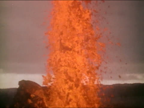 1970s wide shot plume of lava erupting from Kilauea / tilt down to mouth of volcano / Hawaii / AUDIO
