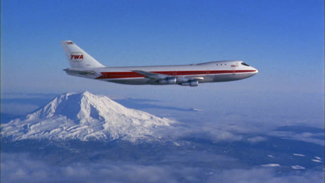 1970s wide shot twa 747 jet plane flies above clouds w/snow-capped mountain in background - commercial airplane stock videos & royalty-free footage