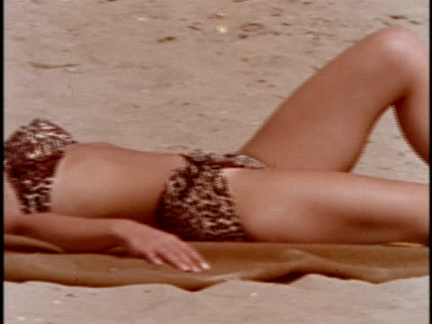 1970s ms pan woman in bikini sunbathing on beach / los angeles, california - swimwear stock videos & royalty-free footage