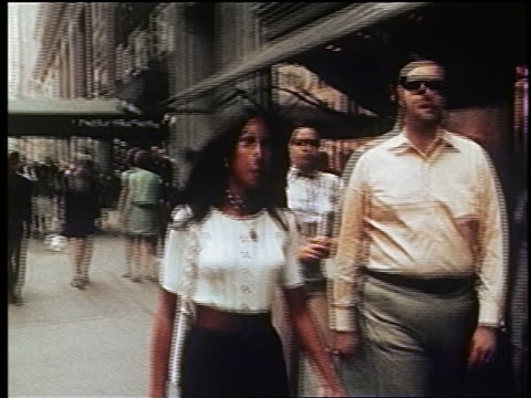 1970s PAN woman in dress carrying purse walking on NYC sidewalk / documentary
