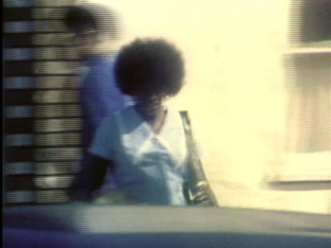 1970s MS TS Woman walking along sidewalk / Los Angeles, California / AUDIO