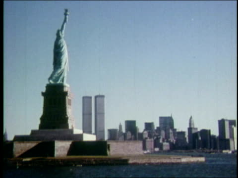 1970s ws world trade center towers and downtown skyline with statue of liberty in foreground / new york city - 1970 stock videos & royalty-free footage
