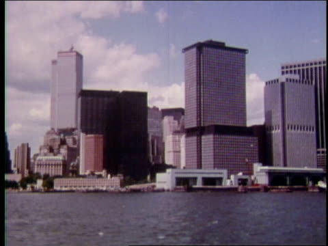 stockvideo's en b-roll-footage met 1970s ws world trade center towers, other downtown manhattan buildings, battery park, & staten island ferry terminals from new york harbor - veerboothaven