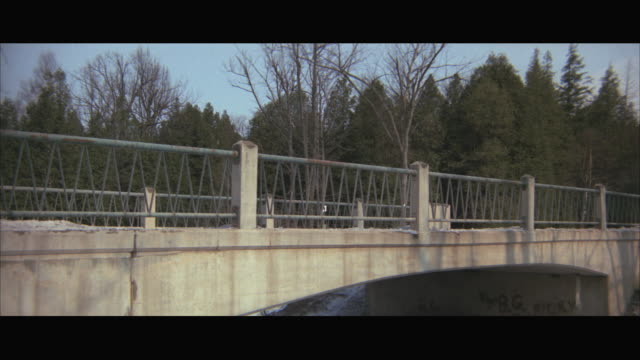 1970s WS Yellow taxi cab driving along bridge in country