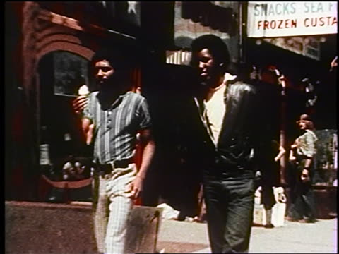 1970s zoom out two black men walking on nyc sidewalk / one eating ice cream cone, one in leather jacket - african american ethnicity stock videos & royalty-free footage