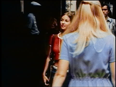 1970s zoom out pan young woman in cropped t-shirt + hiphugger jeans walks on nyc sidewalk with shopping bag - t shirt stock videos & royalty-free footage