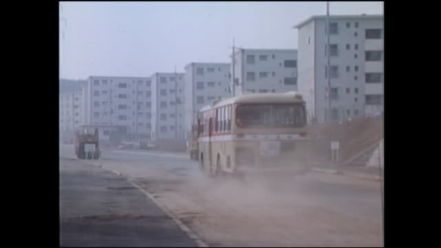 1971,tama new town,bus runs to make a cloud of dust - 1971 stock-videos und b-roll-filmmaterial