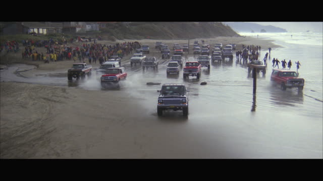 1980s aerial ws ts off-road vehicle rally on beach - 4x4 video stock e b–roll