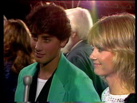 1980s ms celebrities at premiere olivia newton john and matt lattanzi being interviewed / los angeles california usa / audio - olivia newton john stock videos & royalty-free footage