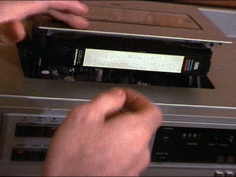 vídeos de stock e filmes b-roll de 1980s close up hand pushing tape into vhs deck / ejecting tape from vcr and removing it - videocassete