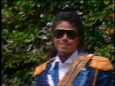 1980s close up Michael Jackson standing between Ronald Nancy Reagan outdoors at award ceremony