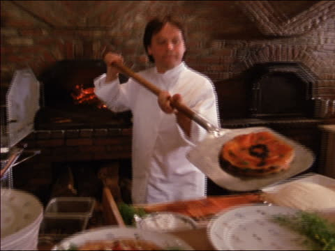 1980s close up zoom out chef wolfgang puck taking pizza out of pizza oven and setting it on plate / los angeles - cooking utensil stock videos & royalty-free footage