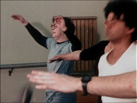 stockvideo's en b-roll-footage met 1980s close up zoom out men and woman kicking up legs during an aerobics class - schoppen lichaamsbeweging