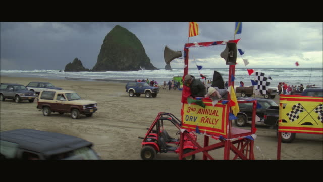 stockvideo's en b-roll-footage met 1980s ws crowd gathered on beach for start of off-road vehicle rally - westers schrift