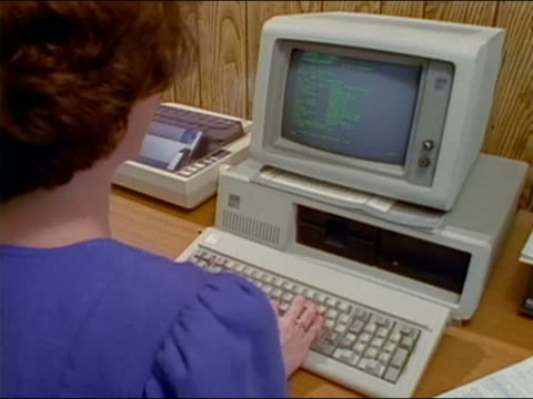 1980s high angle medium shot woman typing on computer - vintage computer monitor stock videos & royalty-free footage