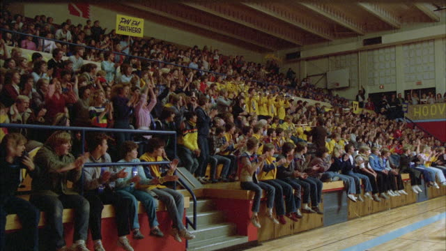 1980s WS High school gymnasium wrestling match. Band plays in stands with crowd, crowd reacts.