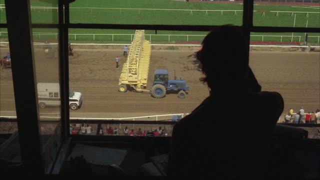 vídeos de stock, filmes e b-roll de 1980s ws ha interior of press box, man silhouetted in foreground watching start of horse race - grupo médio de animais