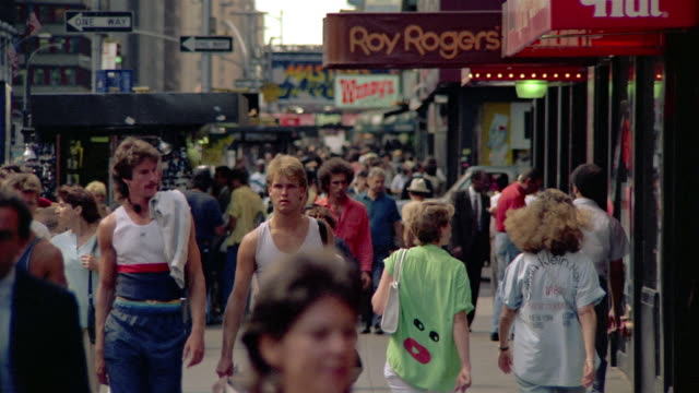 1980s long shot people walking on crowded city street / new york city - 1980~1989年点の映像素材/bロール