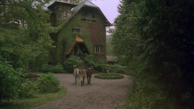 1980s ws man walking horses from mansion to and by camera - 1980 1989 stock videos & royalty-free footage