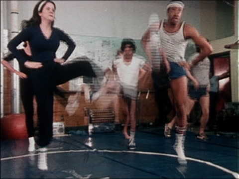 1980s medium shot men and women kicking their legs up during an aerobics class