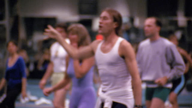 1980s medium shot pan men and women working out in aerobics class / man leading class / los angeles - aerobics stock videos & royalty-free footage