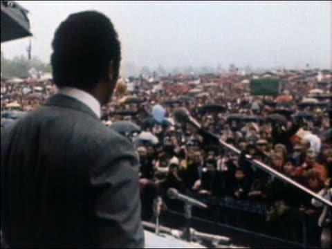 1980s medium shot rear view of jesse jackson speaking before large crowd at rainy antinuke demonstration - kernenergie stock-videos und b-roll-filmmaterial