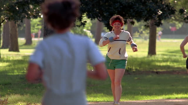 1980s medium shot smiling woman race walking through park while wearing wrist weights / Houston