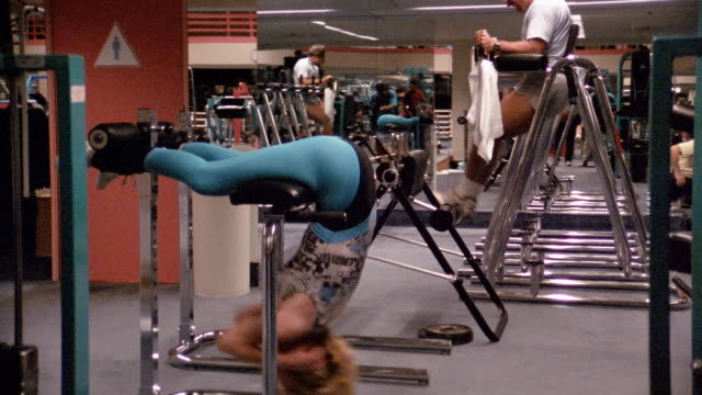 1980s medium shot woman exercising on workout bench - lycra stock-videos und b-roll-filmmaterial
