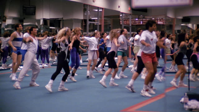 vídeos de stock e filmes b-roll de 1980s medium shot zoom out men and women working out in aerobics class - body de ginástica