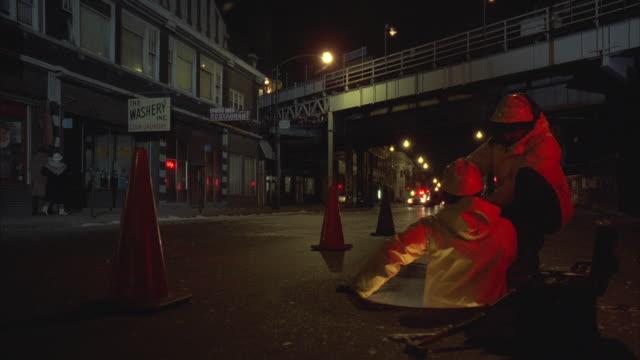 1980s ws men working in manhole at night, fire trucks running by / chicago, illinois, usa - addetto alla manutenzione video stock e b–roll