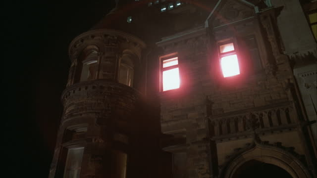 1980s ws la older three story brownstone apartment building with illuminated windows - gothic stock videos & royalty-free footage