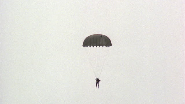 1980s ws td parachutist with old fashioned round military parachute landing in jungle - パラシュート点の映像素材/bロール