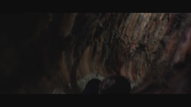 1980s WS POV Person moving down water slide in cave