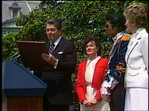 1980s Ronald Reagan giving giving speech then giving plaque to Michael Jackson outdoors